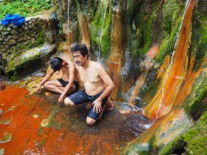 Des locaux sous les douches chaudes des sources de Belulang. Le souffre et le fer présents dans l'eau laissent les couleurs visibles sur les murs