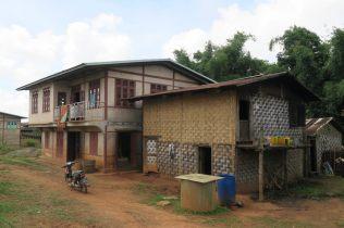 """Ici les maisons sont traditionnellement en bambou (à droite), puis avec le temps (et l'argent) certaines famille arrivent à construire """"en dur"""" (à gauche)"""