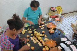 les femmes découpent les feuilles d'or aplaties pour les mettre en carrés. Elles seront ensuite vendues