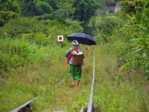 Une mère portant son enfant (devant), ses marchandises et un parapluie