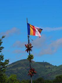 Un drapeau bouddhiste, en haut d'un mat sur une barge