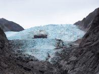 Gros plan sur le glacier Franz Josef, sa glace bleue et sa poussière de roche