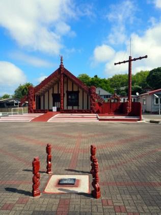 """Dans le village Maori de Ohinemutu, la place principale avec la """"maison commune"""" de la communauté"""