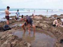 """Julien emprunte une pelle ainsi qu'un """"trou"""" existant et tente de l'améliorer... Les places sont chères, et tous les """"trous"""" ne se valent pas à """"Hot Water Beach"""" !"""