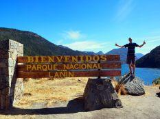 Julien devant le panneau d'entrée du parc national Lanin, avec derrière le Lago Lacar, San Martin de Los Andes