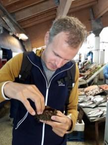 Julien déguste un oursin au port de pêche de Valparaiso