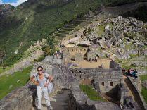 """Elise dans la partie urbaine du site du Machu Picchu, avec en arrière plan la """"place sacrée"""" du site (plateforme autour de laquelle furent construit les bâtiments à caractère religeux)"""