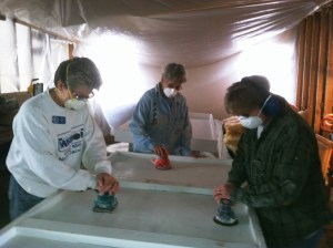 Jenny, Carlie and Pam painting, sanding, and painting two loft bunks to be hung in a residence building at the Orchard.