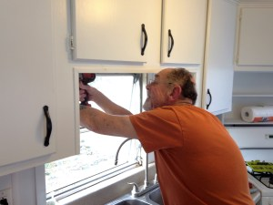 Bruce installing new window dressing above the kitchen sink.
