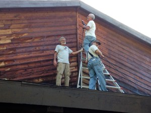 "Jerry, Ken and John power washed and stained ""The Barn"", the biggest buiding in the camp. Looks great. Here they are on the roof doing the upper level."