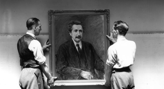 Two men prepare to hang a portrait of Albert Einstein by Max Liebermann at an exhibition of 'degenerate' German art at the New Burlington Galleries, London. The exhibition includes work by all the German artists pilloried by Adolf Hitler in the 'Degenerate Art' exhibition in Munich of 1937.