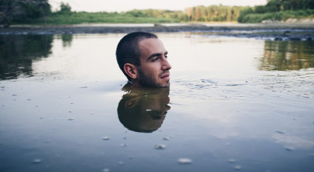 A young man keeps his head above water as he looks on at the shoreline and trees.