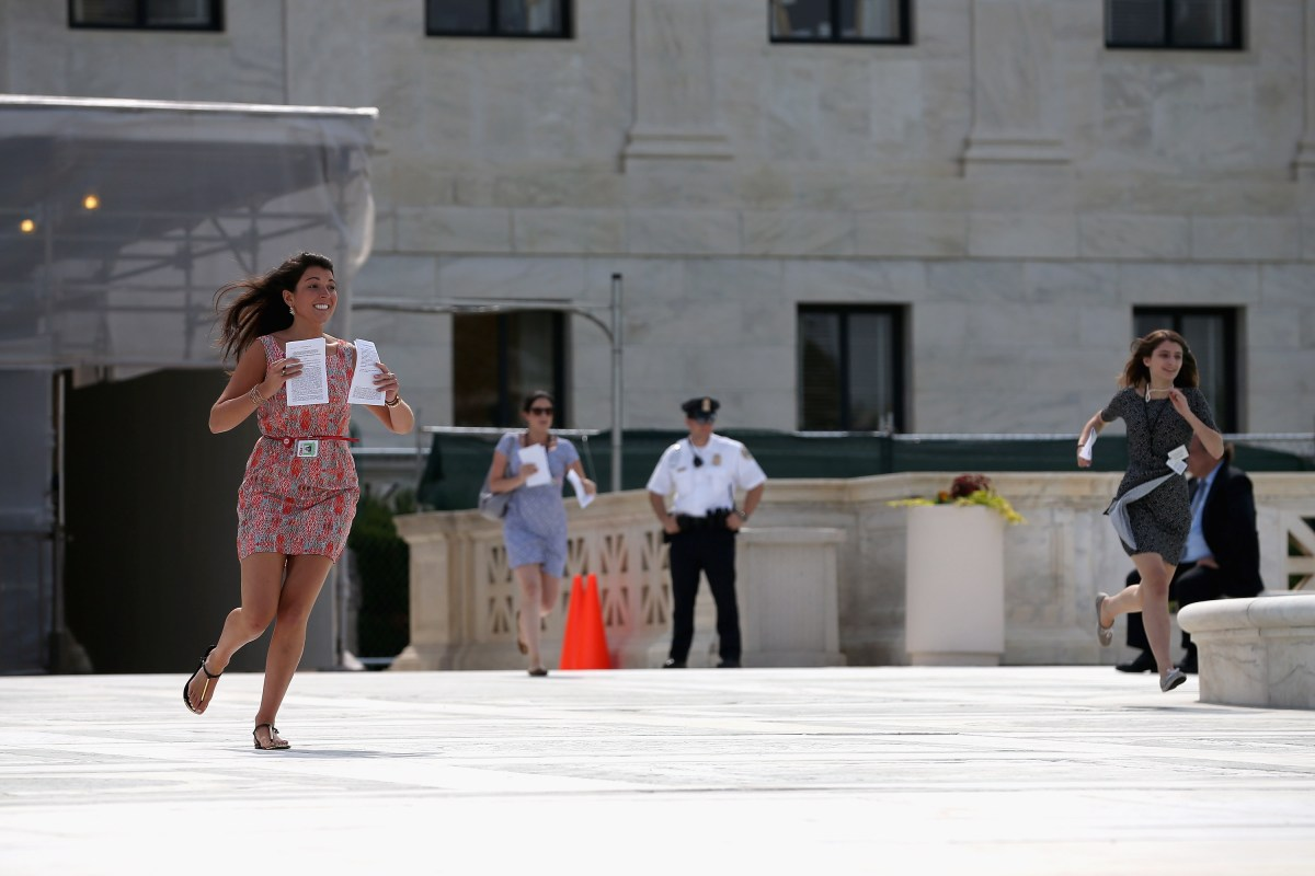 A CNN employee runs after a Supreme Court ruling was made on race-based college admissions on June 24, 2013 in Washington DC. (Photo by Mark Wilson/Getty Images)