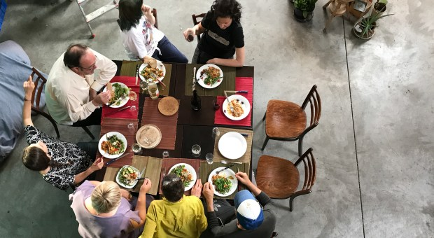 People gather around the communal dining table.