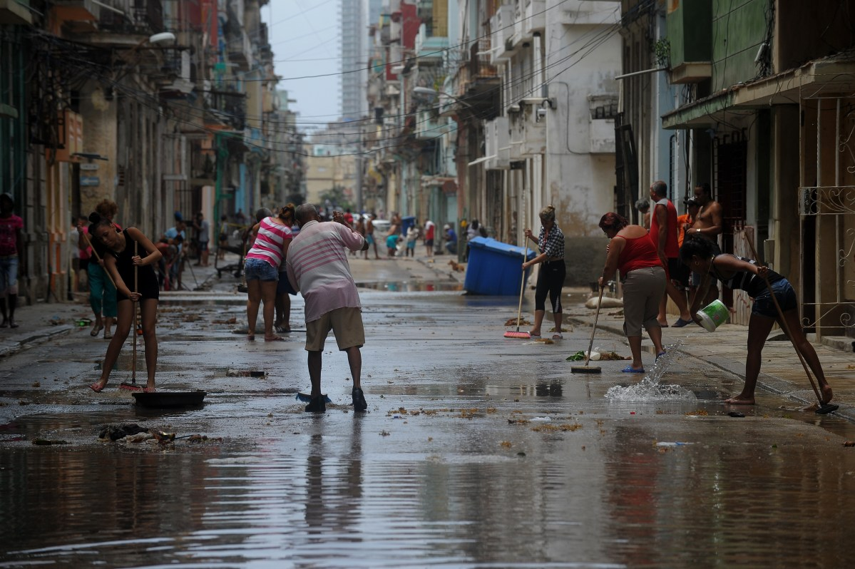 Cubans clean a street of Havana, on September 10, 2017. Deadly Hurricane Irma battered central Cuba on Saturday, knocking down power lines, uprooting trees and ripping the roofs off homes as it headed towards Florida. Authorities said they had evacuated more than a million people as a precaution, including about 4,000 in the capital. (Photo credit should read YAMIL LAGE/AFP/Getty Images)