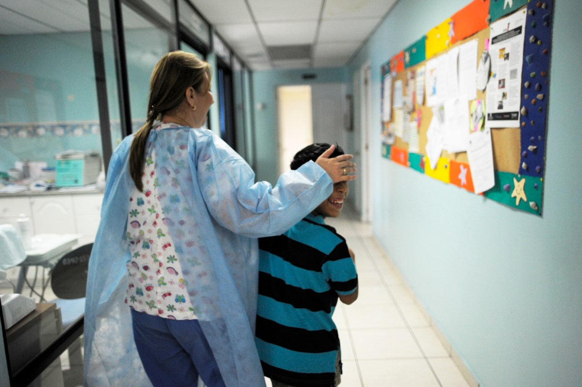 A dentist jokes with a patient at The Center of Excellence for Children with Immunodeficiencies (CENID) at the Benjamin Bloom National Children Hospital in San Salvador, El Salvador on November 28, 2012.