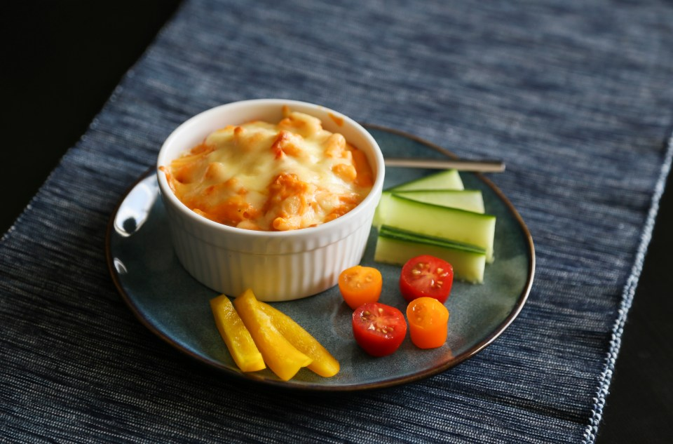 Sweet potato macaroni and cheese in a white ramekin on a dark blue plate with some fresh vegetables.