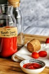 A bottle with homemade tomato sauce (ketchup) with cork and scattered cherry tomatoes.