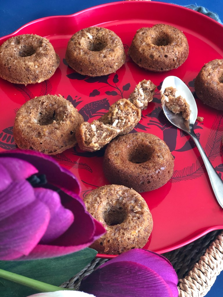 Healthier baked carrot cake donuts on a red plate.