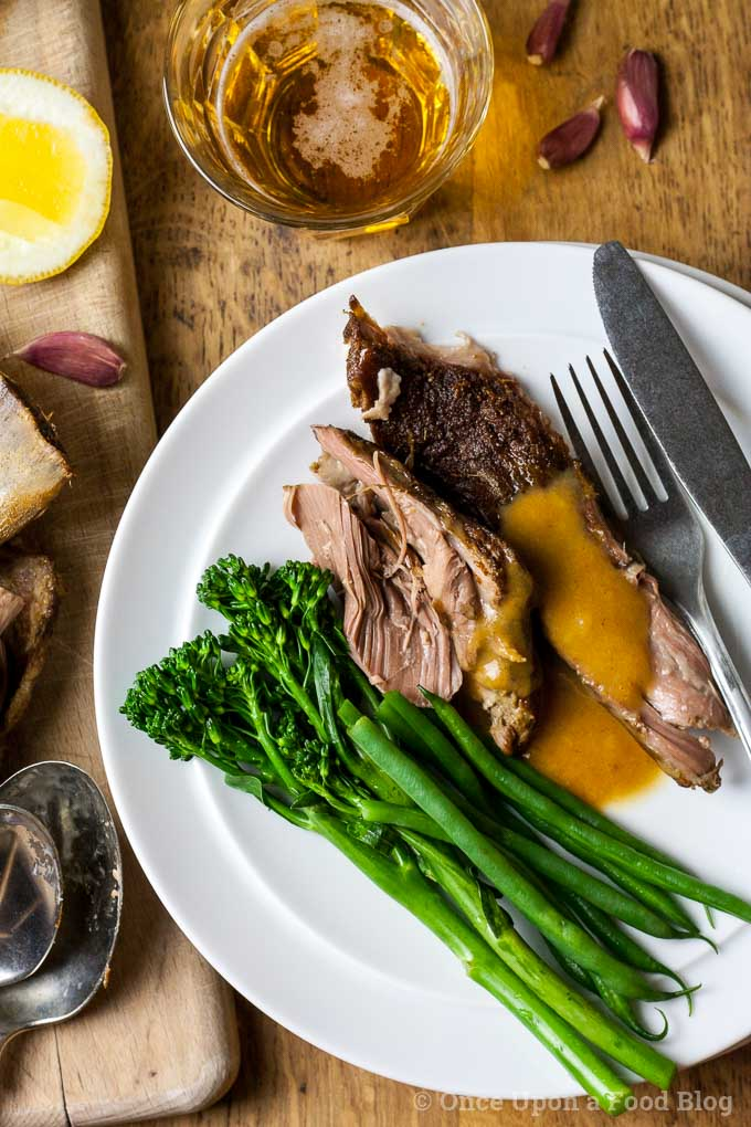 A plate of lamb served with gravy, green beans and tender stem broccoli