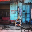 A little girl sits on the streets of Guatemala City, watching as protestors walk by to commemorate Guatemala's revolution of October 20 1944