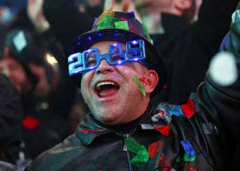 A man celebrates the arrival of 2019 under a shower of confetti during the New Year's Eve celebration in Times Square, New York, on January 1, 2019. (AP Photo / Adam Hunger)