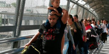 In this photograph from April 29, 2019, Cuban migrants are escorted by Mexican immigration authorities in Ciudad Juárez, Mexico. (AP Photo/Christian Torres)