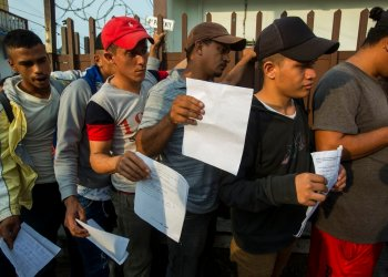 Central American migrants line up outside the Mexican Refugee Aid Commission in Tapachula to obtain the necessary documents that allow them to stay in Mexico, on Thursday, June 20, 2019. Photo: Oliver de Ros / AP.