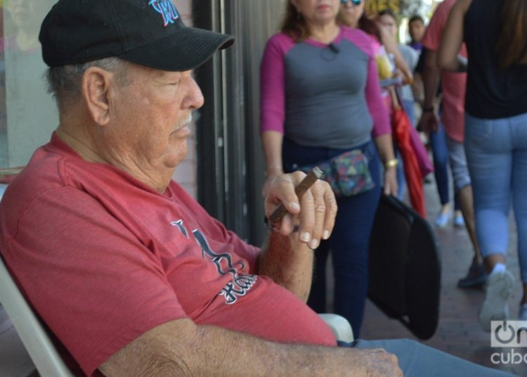 A Cuban smokes a cigar and dozes in front of his business on Calle Ocho. Photo: Marita Pérez Díaz.