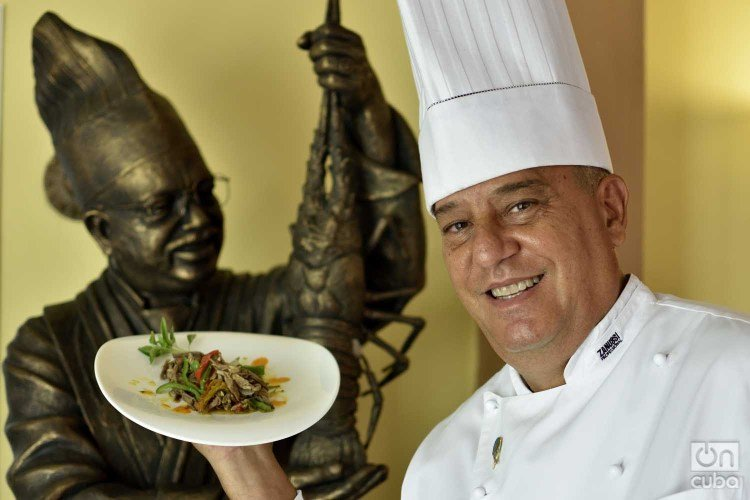 Chef Eddy Fernández, president of the island's Federation of Culinary Associations and a tireless defender of Cuban cuisine. Behind, a statue of chef Gilberto Smith, founder of the Federation and one of the essential figures of culinary art on the island. Photo: Otmaro Rodríguez.