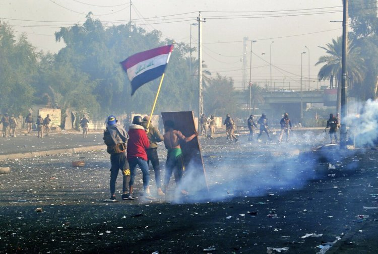 Protesters waving the national flag while security forces launch tear gas at a protest in central Baghdad, Iraq, on Monday, January 20, 2020. Photo: AP/Hadi Mizban