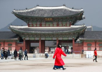A woman with her mouth covered by a mask walks in front of Gyeongbokgung Palace, one of South Korea's best known monuments in Seoul, on February 22, 2020. (AP Photo/Lee Jin-man)