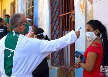 Taking the temperature before testing for COVID-19, in a section of Los Sitios, in Havana. Photo: Otmaro Rodríguez