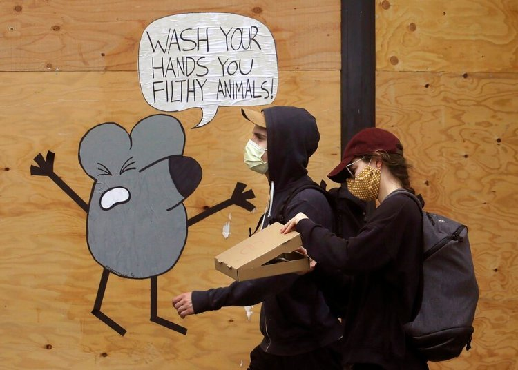 A man and a woman wearing facemasks walk past a mural reminding people to wash their hands, on a plank-protected store in San Francisco. Photo: Jeff Chiu/AP