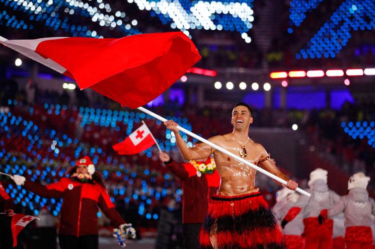 Pita Taufatofua, de Tonga, porta la bandera de su país durante la ceremonia de inauguración de los Juegos Olímpicos de Invierno en Pyeongchang. Foto: Jae C. Hong / AP.