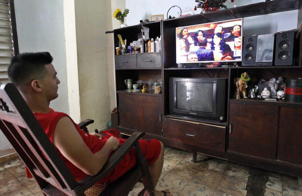 Un hombre ve desde su casa la programación especial de la Televisión Cubana donde se transmite en vivo la sesión constitutiva de la IX Legislatura de la Asamblea Nacional del Poder Popular. Foto: Ernesto Mastrascusa / EFE.