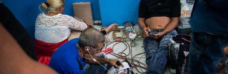 Un comercio local les presta la electricidad para que los cubanos puedan mantener cargados sus celulares. Foto: Irina Dambrauskas.