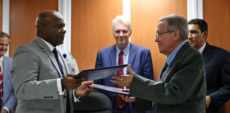 Darrell McNail (izquierda), presidente del Consejo de la Administración del puerto de Cleveland, y el capitán José Joaquín Prado, Director General de la Administración Marítima de Cuba, intercambian los documentos ya firmados. Foto: Alejandro Ernesto / EFE.