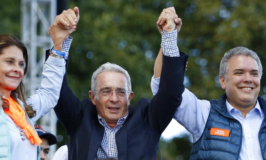 El ex presidente colombiano Álvaro Uribe sonríe entre Iván Duque, aspirante presidencial por el Partido Centro Democrático, derecha, y su compañera de fórmula Martha Lucía Ramírez durante un mítin de campaña en Bogotá, el domingo 20 de mayo de 2018. Foto: Fernando Vergara/AP.
