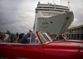 Turistas que recorren La Habana pasan por delante de un crucero atracado en el puerto de la capital de Cuba. Foto: Ramón Espinosa / AP.