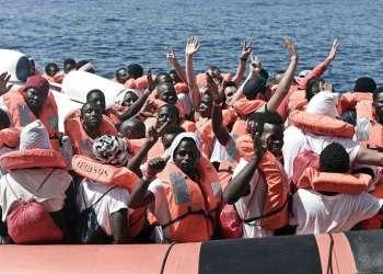 Migrantes saludan durante su traslado del barco Aquarius a otro de la Guardia Costera italiana, en el Mar Mediterráneo. Foto: Kenny Karpov / SOS Mediterranee vía AP.