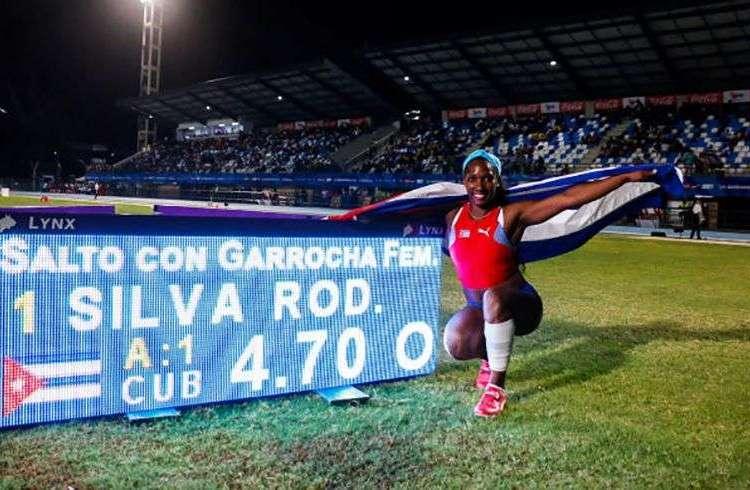 La pertiguista cubana Yarisley Silva posa junto a su récord en salto con pértiga del atletismo en los Juegos Centroamericanos de Barranquilla. Foto: Calixto N. Llanes / JIT.