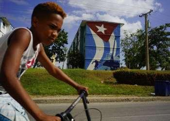Fotografía del 25 julio de 2018 de un joven montando su bicicleta frente a un edificio con un mural de la bandera cubana y Fidel Castro saltando de un tanque durante la invasión de Bahía de Cochinos, en la ciudad de Guantánamo, Cuba, vecina de la Base Naval de Estados Unidos en la Bahía de Guantánamo. Aunque Fidel Castro murió hace casi dos años, su recuerdo sigue vivo en los dos Guantánamos. (AP Foto/Ramón Espinosa)