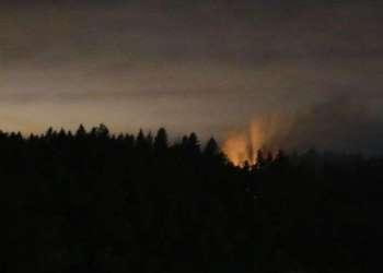 Humo y un resplandor naranja sobre la isla Ketron, en el estado de Washington. Un empleado de aerolínea se robo un avión desocupado de Horizon Air y momentos después se estrelló con la aeronave en la isla. Foto: Ted S. Warren/AP.