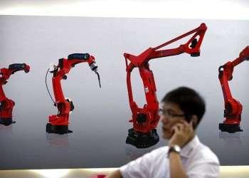 Un visitante habla por su smartphone delante de una imagen de robots de la empresa china Honyen, en el World Robot Conference, en Beijing, China. Foto: Mark Schiefelbein / AP.