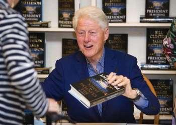 """El presidente Bill Clinton sostiene una copia de """"The President is Missing"""" en Book Revue, en Huntington, Nueva York. Foto: Scott Roth / Invision / AP / Archivo."""