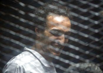 """Mahmoud Abu Zaid, un fotoperiodista conocido como """"Shawkan"""" y cuya detención ha sido denunciada por grupos de derechos humanos en su país y en el extranjero, es visto detrás de una malla metálica en un tribunal en El Cairo, el sábado 8 de septiembre de 2018. Foto: Roger Anis / AP."""