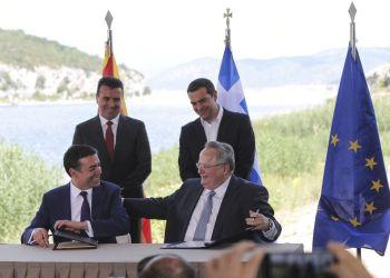 El primer ministro de Grecia, Alexis Tsipras (atrás, derecha), y su homólogo de Macedonia, Zoran Zaev (atrás, izquierda), observan mientras el ministro griego de Exteriores, Nikos Kotzias (derecho), y su contraparte macedonia, Nikola Dimitrov, firman un acuerdo para el nuevo nombre de Macedonia en la localidad de Psarades, en Grecia el 17 de junio de 2018. Foto: Yorgos Karahalis / AP.