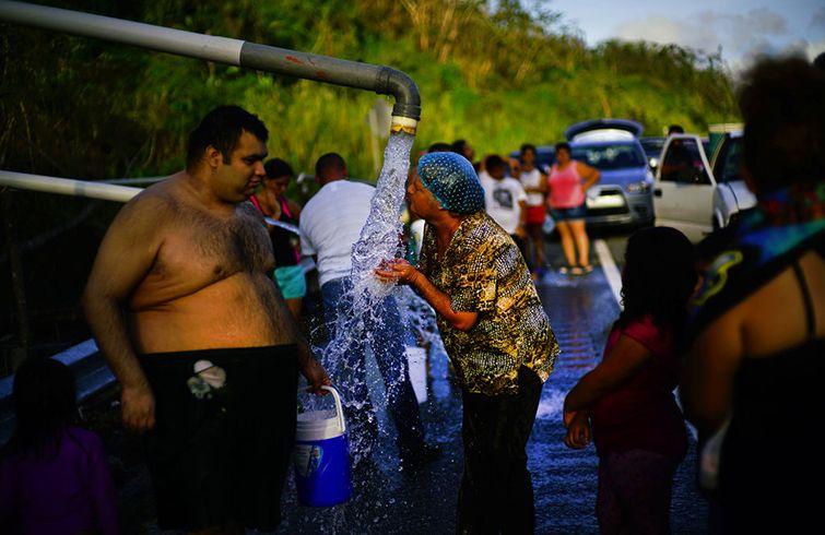 Residentes de Utuado, Puerto Rico, se aglomeran frente a tuberías que traían agua de un riachuelo el 14 de octubre del 2017, tras el paso del huracán María que causó devastación en la isla. Foto: Ramón Espinosa / AP / Archivo.