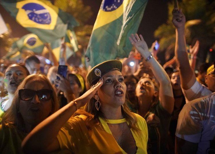 Una simpatizante de Jair Bolsonaro saluda durante la celebración de su triunfo en las elecciones presidenciales afuera de la residencia del candidato en Río de Janeiro, Brasil, el 28 de octubre de 2018. Foto: Leo Correa / AP.